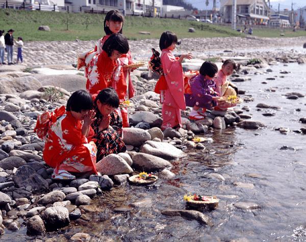 Các bé gái cầu nguyện trong lễ hội búp bê bên bờ suối