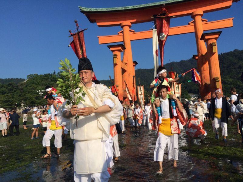 Những người tham gia lễ hội diễu hành qua cổng Torii để lên thuyền